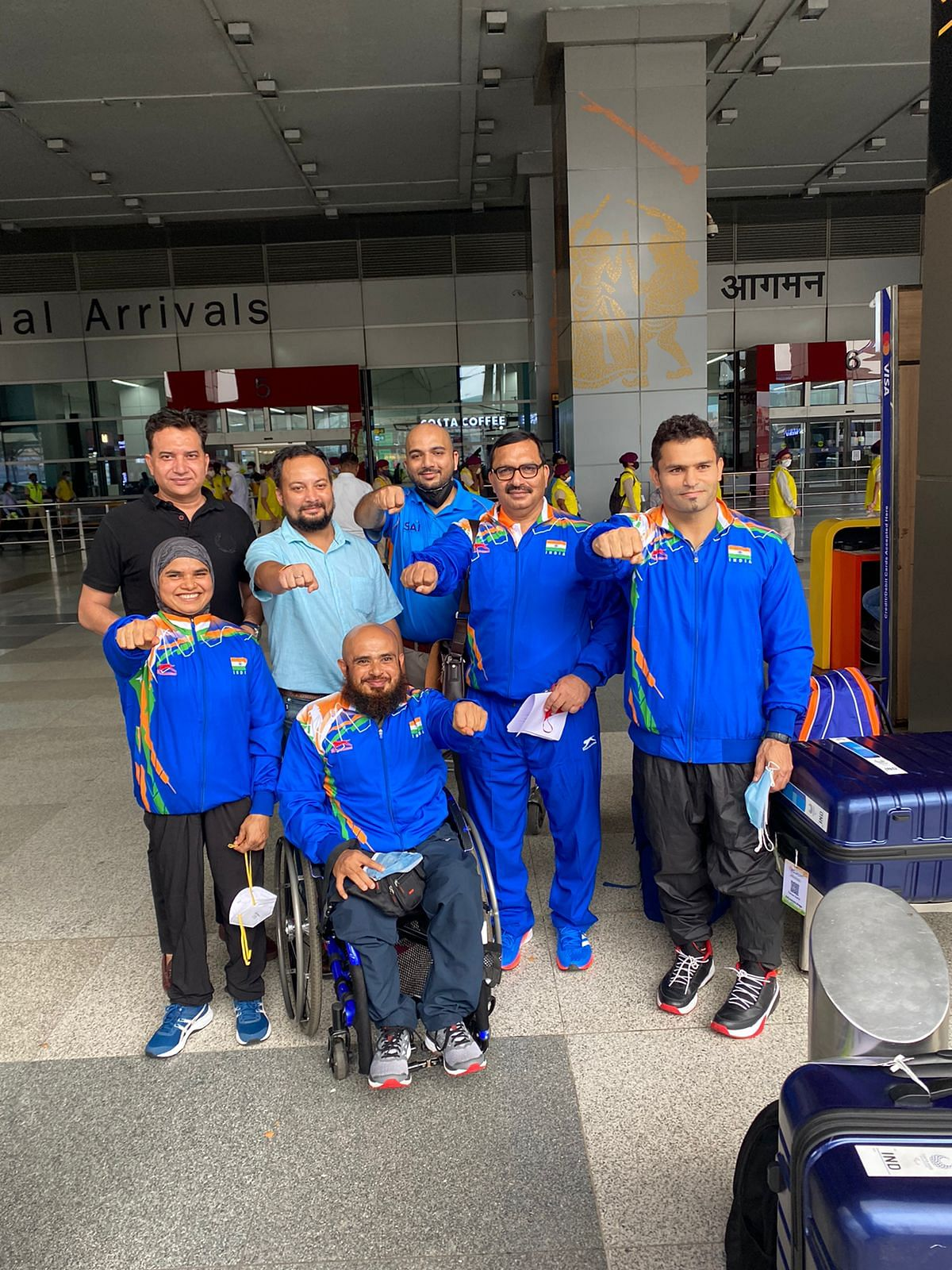 """<div class=""""paragraphs""""><p>Indian Paralympians and support staff pose for a photo at the Indira Gandhi International Airport</p></div>"""