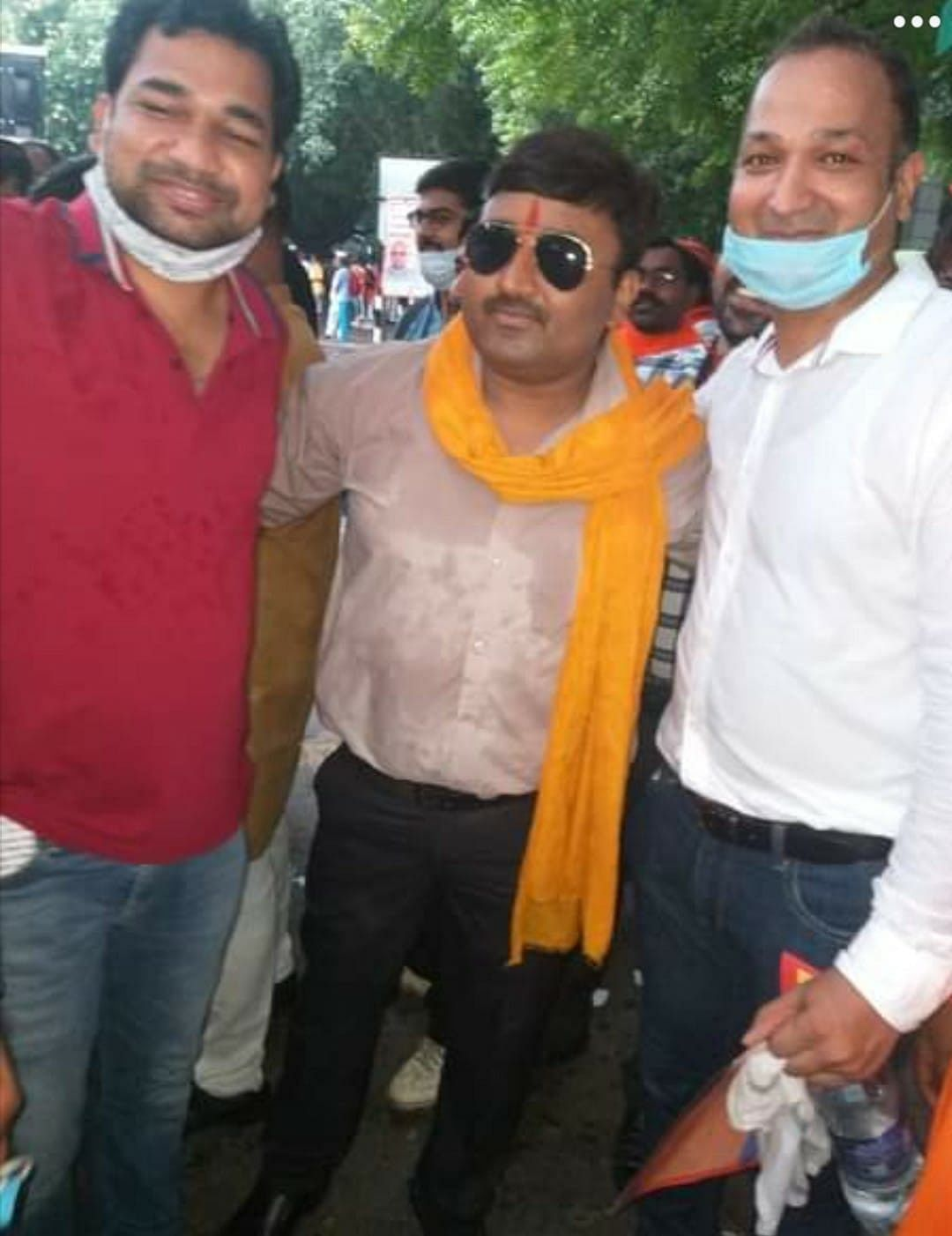 """<div class=""""paragraphs""""><p>In the middle is Deepak Singh posing with two others at the 8 August protest.</p></div>"""