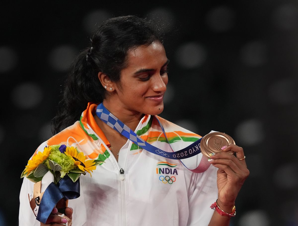 """<div class=""""paragraphs""""><p>Tokyo: India's PV Sindhu poses for photographs while standing on the podium after receiving the bronze medal in women's singles badminton event at the Summer Olympics 2020, in Tokyo, Sunday, August 1, 2021. </p></div>"""