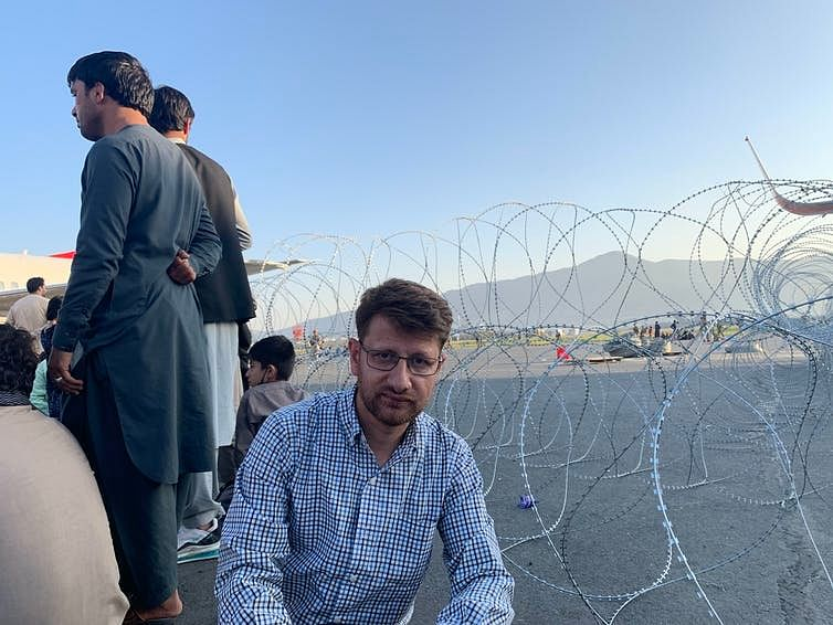 """<div class=""""paragraphs""""><p>Sufizada with others trying to leave Afghanistan at Kabul's Hamid Karzai International Airport. </p></div>"""