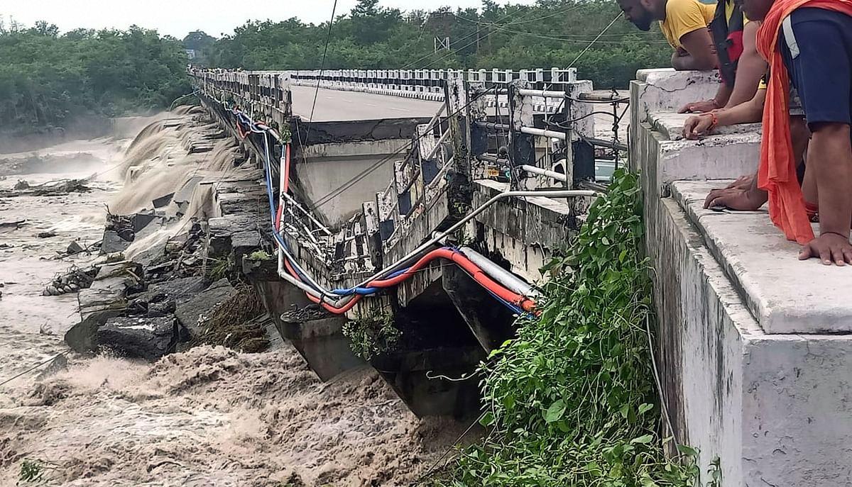 "<div class=""paragraphs""><p>Dehradun: People look at the Rani Pokhri bridge on the Dehradun Rishikesh highway that collapsed due to heavy rains, near Dehradun, Friday, 27&nbsp;August 2021.</p></div>"