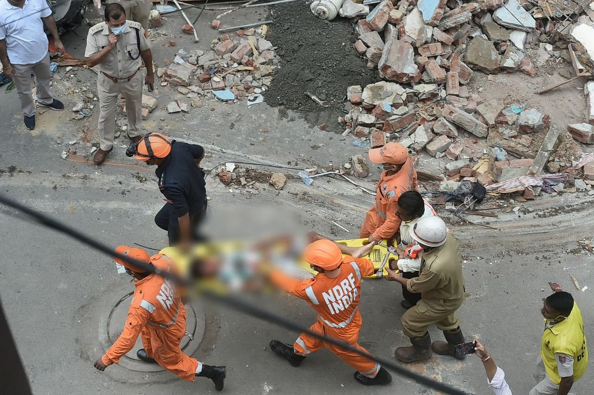 """<div class=""""paragraphs""""><p>NDRF and police personnel carry an injured person during a rescue operation after a building collapsed at Sabji Mandi area. Two kids have been rescued and are in critical condition.</p></div>"""