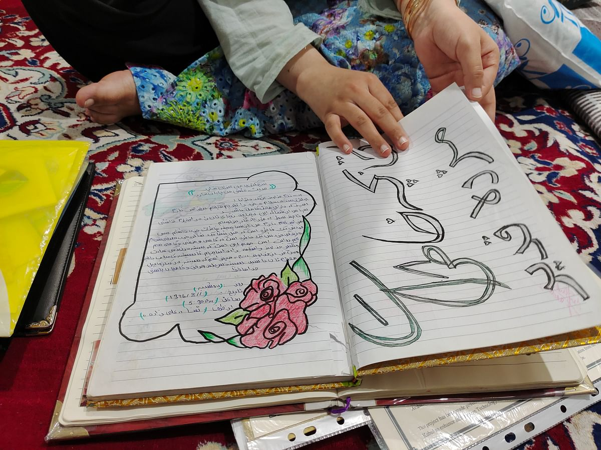 """<div class=""""paragraphs""""><p>A notebook, with her friends' messages, was one of the only things Muzhda carried with her from Afghanistan. She says it is precious.</p></div>"""
