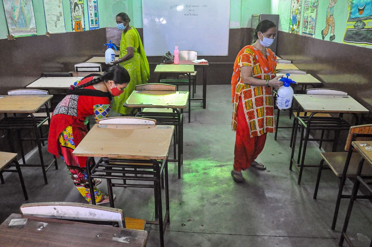 """<div class=""""paragraphs""""><p>Workers sanitise a classroom ahead of its reopening for classes 1 to 5, in Moradabad, Tuesday, Aug 31, 2021. UP government has allowed schools to reopen the junior classes too from 1 September.</p></div>"""