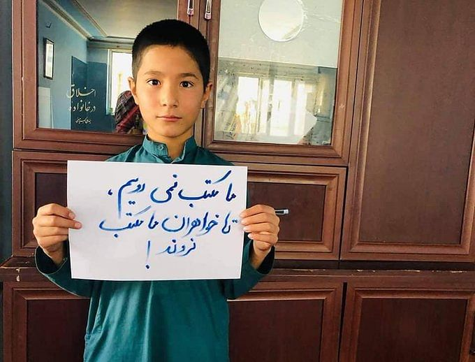 """<div class=""""paragraphs""""><p>An Afghan boy holding a placard that reads, """"We don't go to school without our sisters.""""</p></div>"""