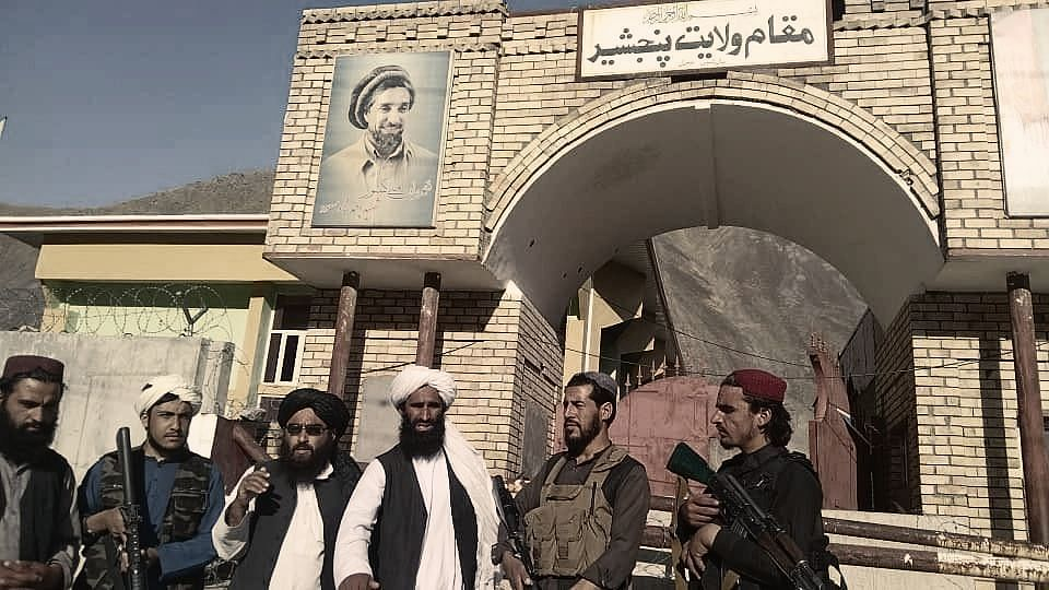 """<div class=""""paragraphs""""><p>Taliban fighters have hoisted their flag at the Panjshir Valley, the stronghold of Taliban opponent Ahmad Shah Massoud (portrait on the wall).</p></div>"""