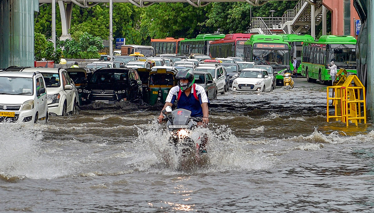 """<div class=""""paragraphs""""><p>New Delhi: Vehicles ply on the waterlogged Tilak Marg after heavy rain at ITO in New Delhi, Wednesday.</p></div>"""