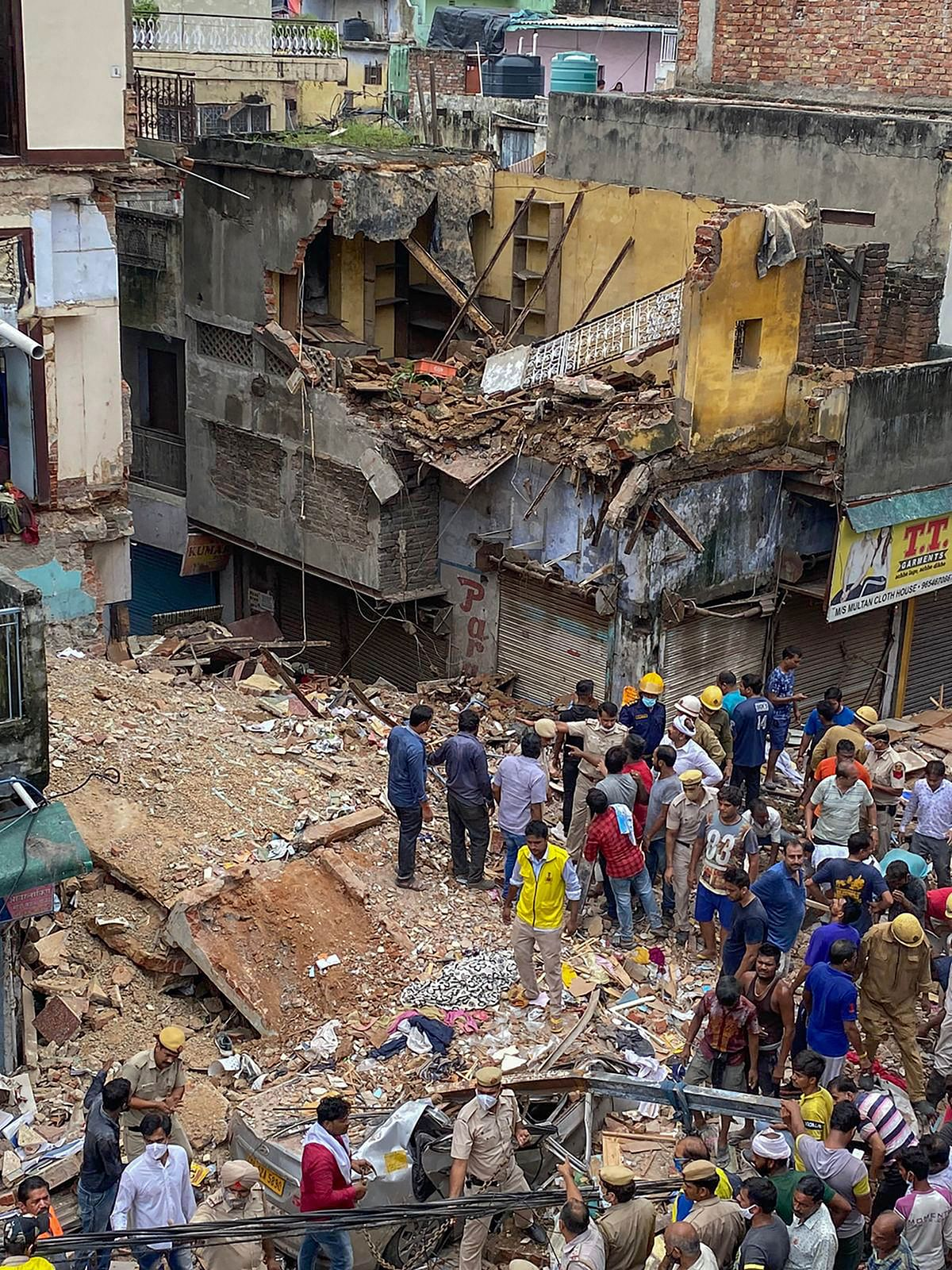 """<div class=""""paragraphs""""><p>New Delhi: People during a rescue operation after a building collapsed at Sabji Mandi area in New Delhi, Monday.</p></div>"""