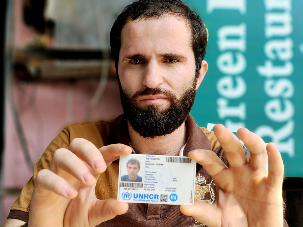 """<div class=""""paragraphs""""><p>Sikander Khan (26) shows his refugee card.&nbsp;Several other Afghan refugees in India have not been able to get these cards from the UNHCR. He hopes this card will help him create a better life for his daughter in a country like Canada.</p></div>"""