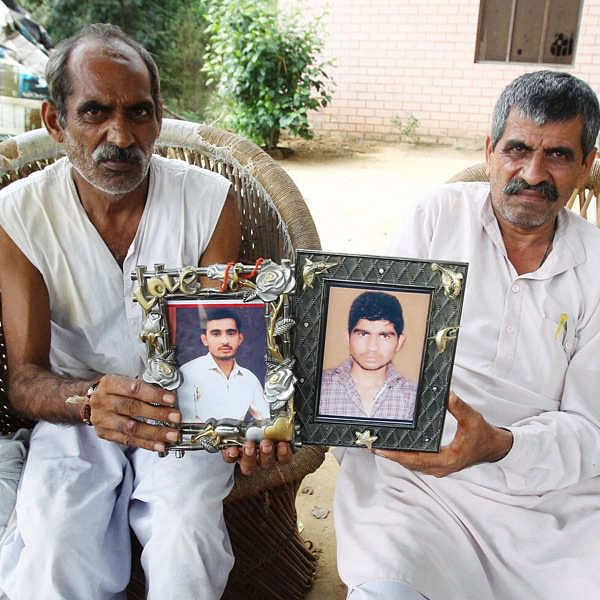 """<div class=""""paragraphs""""><p>This is an image from after the riots.&nbsp;Bisan Singh, father of Sachin (L), and Ravinder Kumar, father of Gaurav, showing the picture of their deceased sons at Kawal village from where the communal riot started, in Muzaffarnagar.</p></div>"""