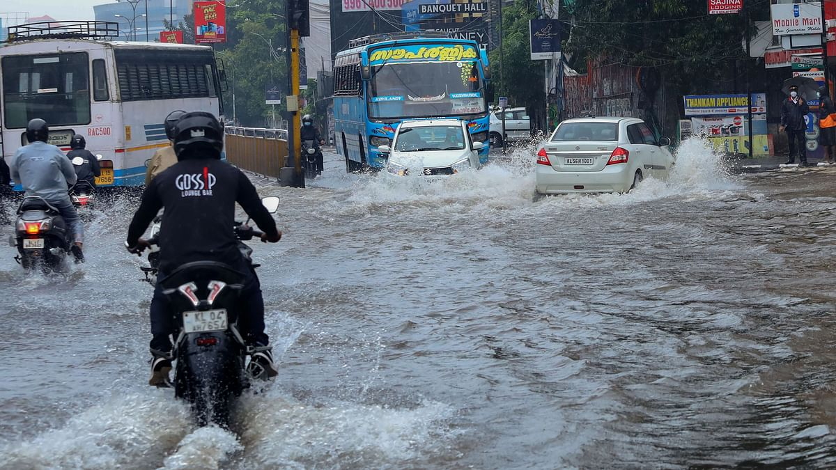 """<div class=""""paragraphs""""><p>Commuters wade through a waterlogged road during heavy rain in Kozhikode, Kerala. Image used for representation purpose.</p></div>"""
