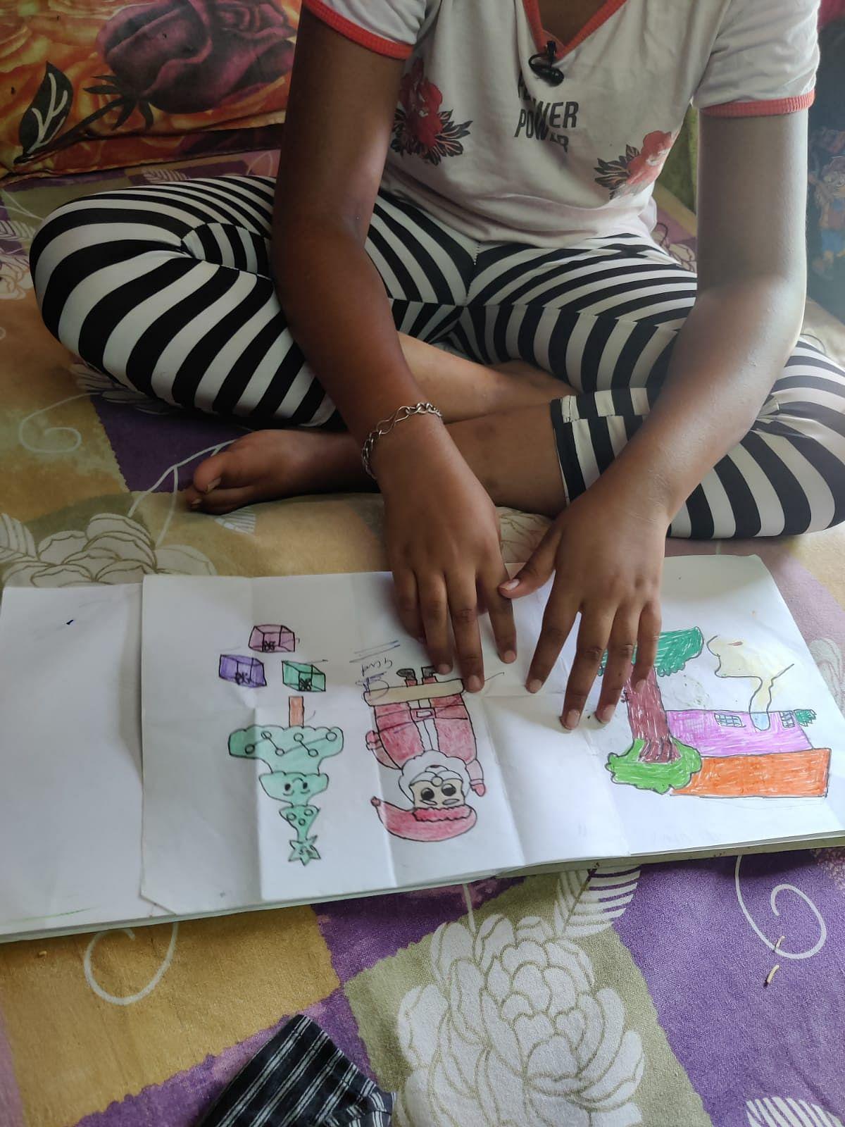 "<div class=""paragraphs""><p>Chhoti Nirbhaya showing her drawings.</p></div>"