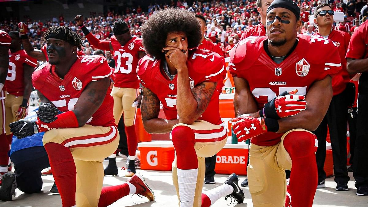 """<div class=""""paragraphs""""><p>Colin Kaepernick (center) with Eli Harold (left) and Eric Reid (right) kneel during the national anthem before their NFL game in 2016.&nbsp;&nbsp;</p></div>"""