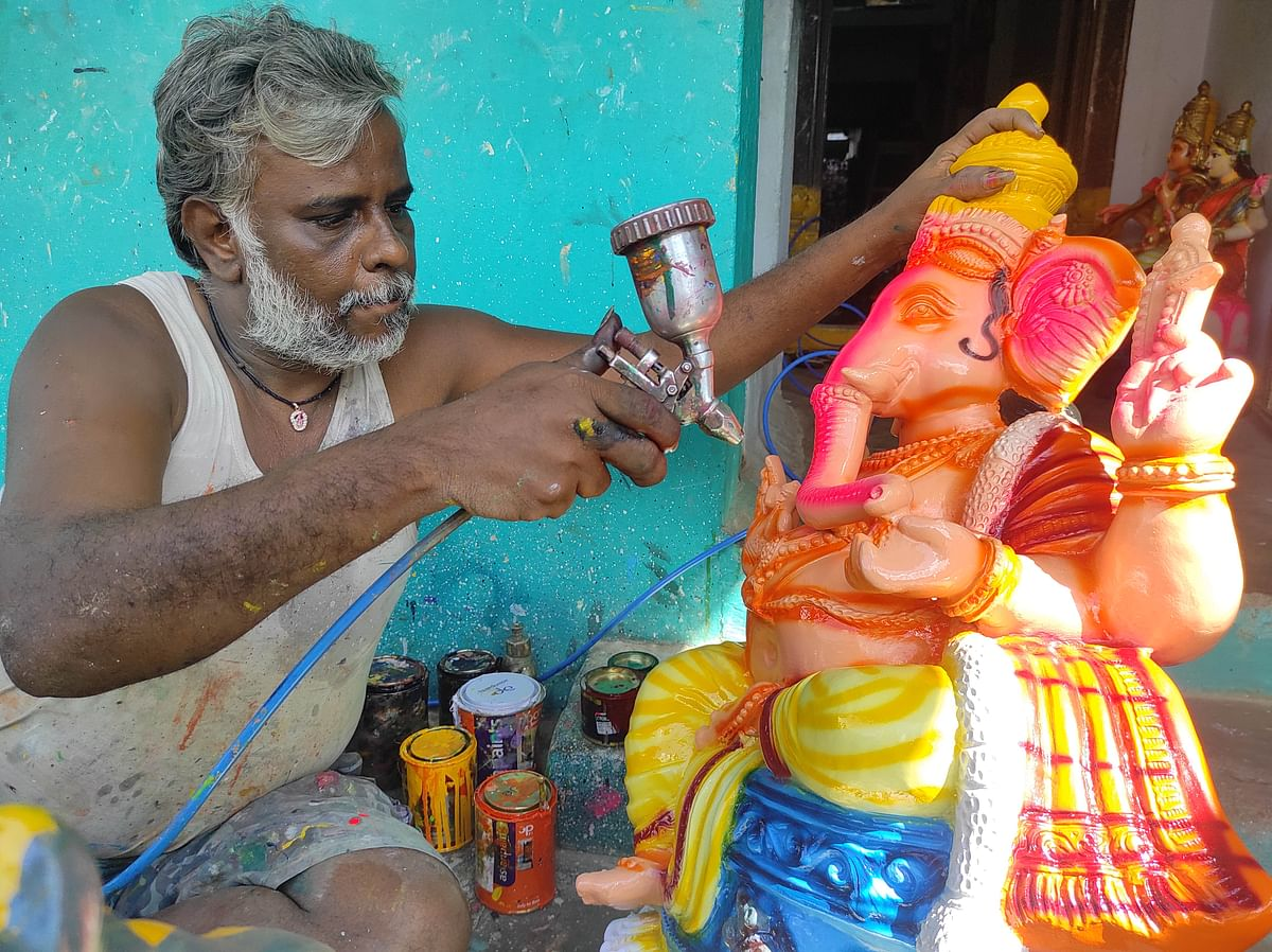 """<div class=""""paragraphs""""><p>Doll maker Suresh giving finishing touches to Vinayaka doll.</p></div>"""