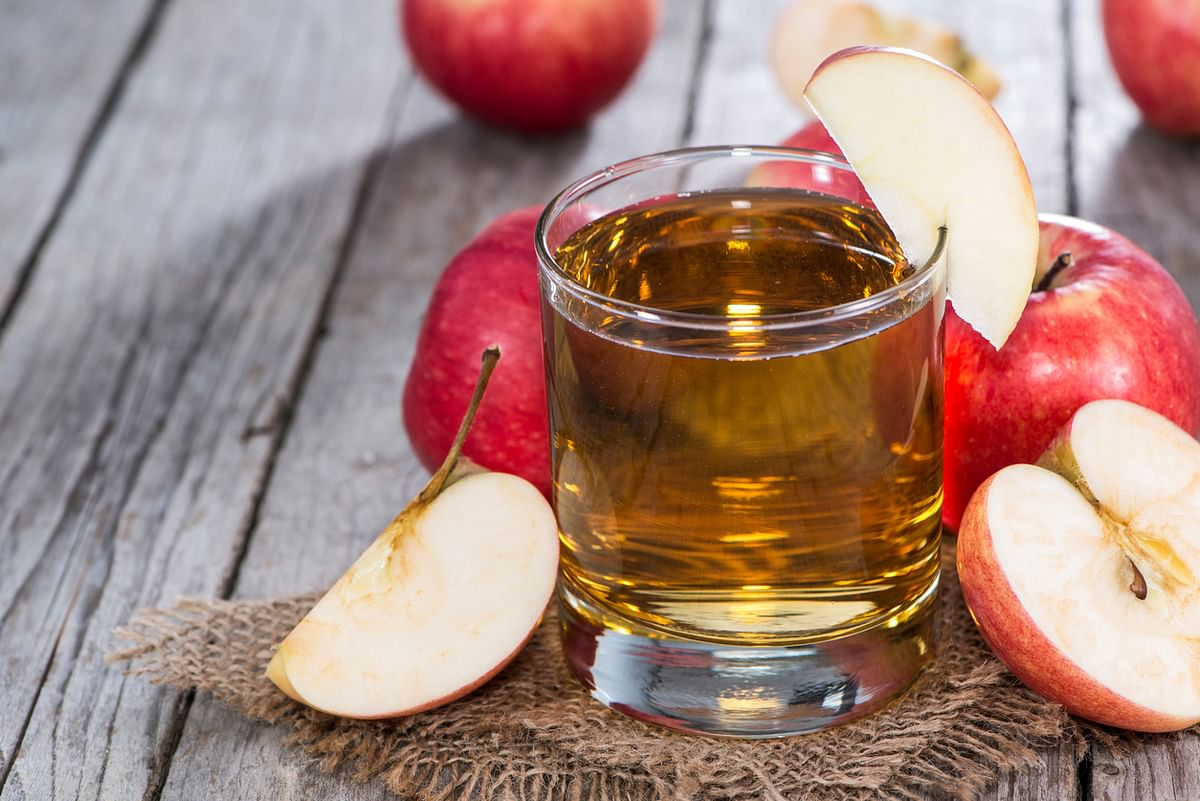 Glass of apple cider surrounded by freshly-cut apples.