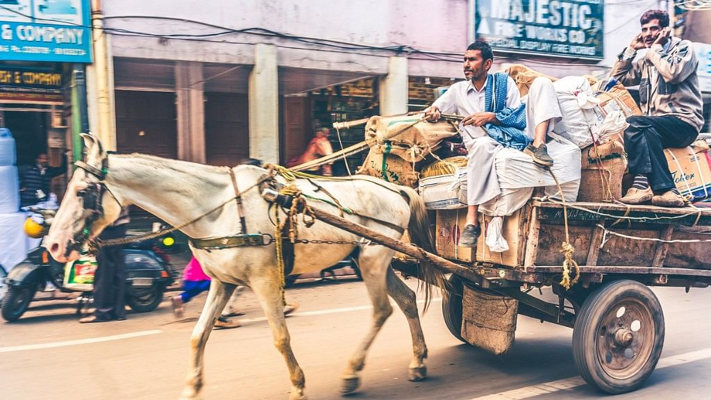 Working horse drawn cart loaded with sacks, bags and boxes ridding in a street of Old Delhi.