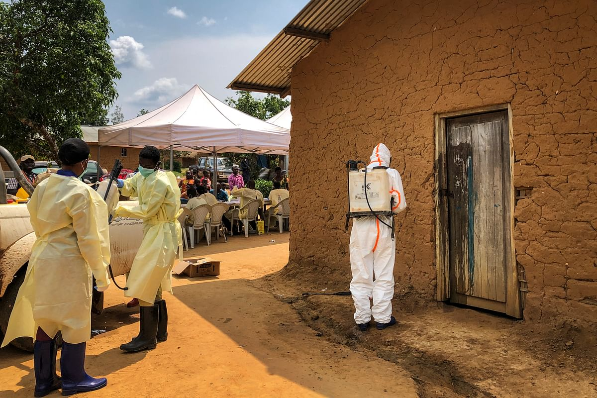 A worker from the World Health Organization (WHO) decontaminates the doorway of a house.