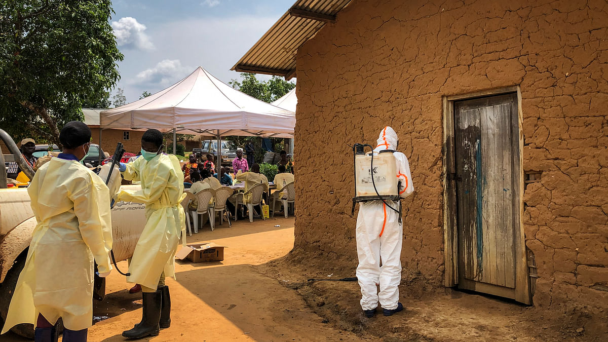 A worker from the World Health Organization (WHO) decontaminates the doorway of a house on a plot where two cases of Ebola were found, in the village of Mabalako, in eastern Congo on Monday, 15 June. Health officials in eastern Congo have begunoffering vaccinations to all residents in the hotspot of Mabalako whereasprevious efforts had only targeted known contacts or those considered to be athigh risk.