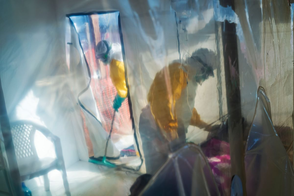 In this photograph taken Saturday 13 July 2019, health workers wearing protective suits tend to to an Ebola victim kept in an isolation cube in Beni, Congo DRC. The Congolese health ministry is confirming the country's first Ebola case in the provincial capital of 2 million, Goma, some 360 kms ( 225 miles) south of Beni. More than 1,600 people in eastern Congo have died as the virus has spread in areas too dangerous for health teams to access.
