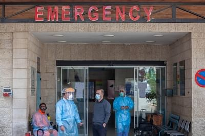 Health staff wearing protective masks standing at the emergency entrance of a Hospital.
