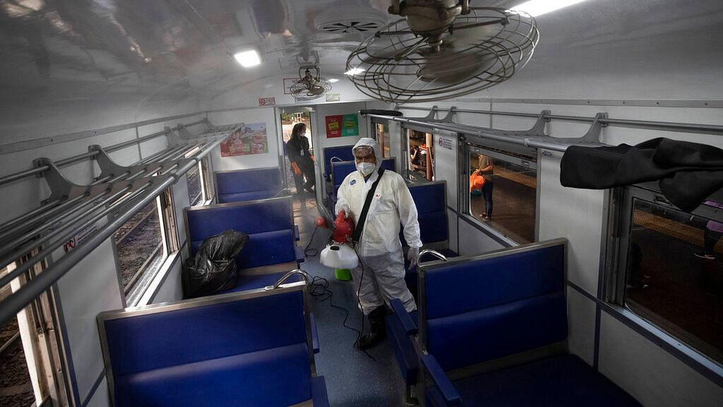 A Thai worker disinfects inside a train to avoid the spread of the new coronavirus at Hua Lamphong Railway Station in Bangkok, Thailand
