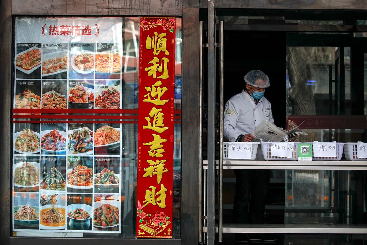 An employee wearing protective gear reads a newspaper at a restaurant only offering take-out orders following the coronavirus outbreak in Beijing, Sunday, March 1, 2020.