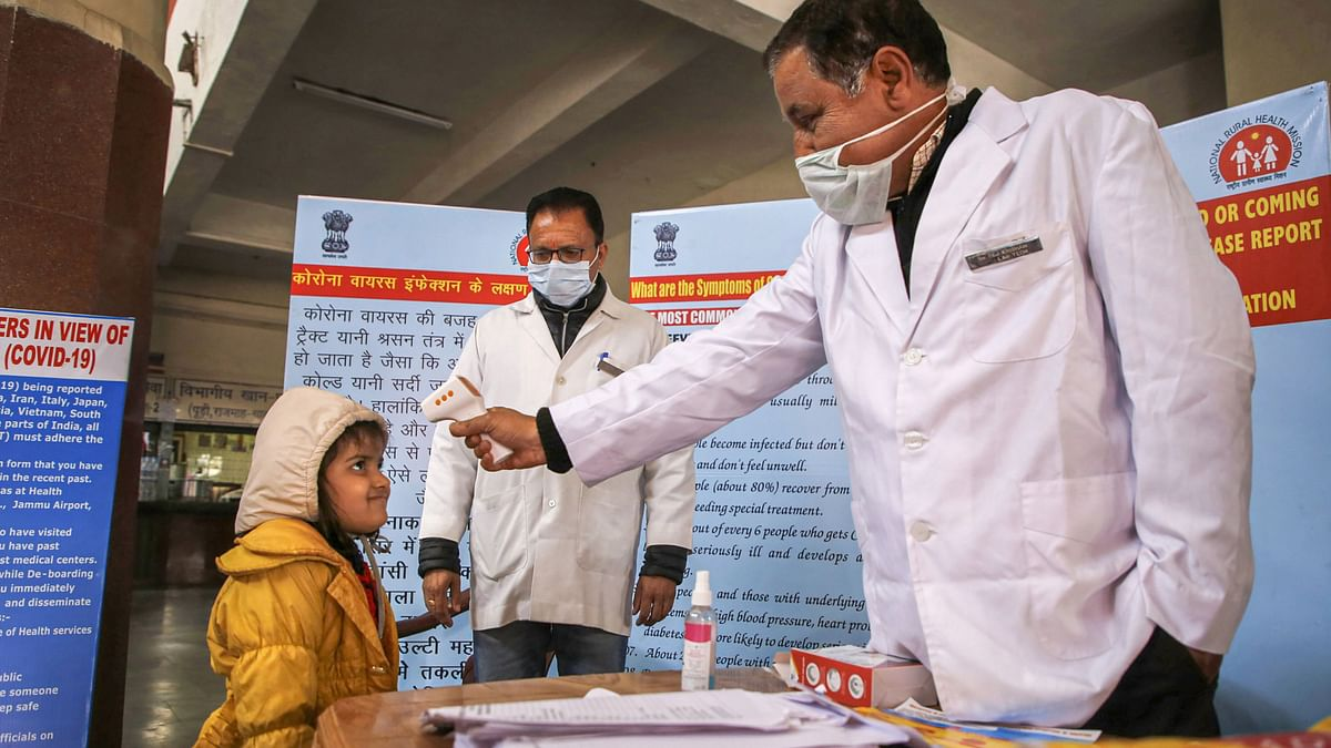 A doctor checks the temperature of a child passenger as part of precautionary measures against the new coronavirus, at a railway station in Jammu, Thursday, March 12, 2020.