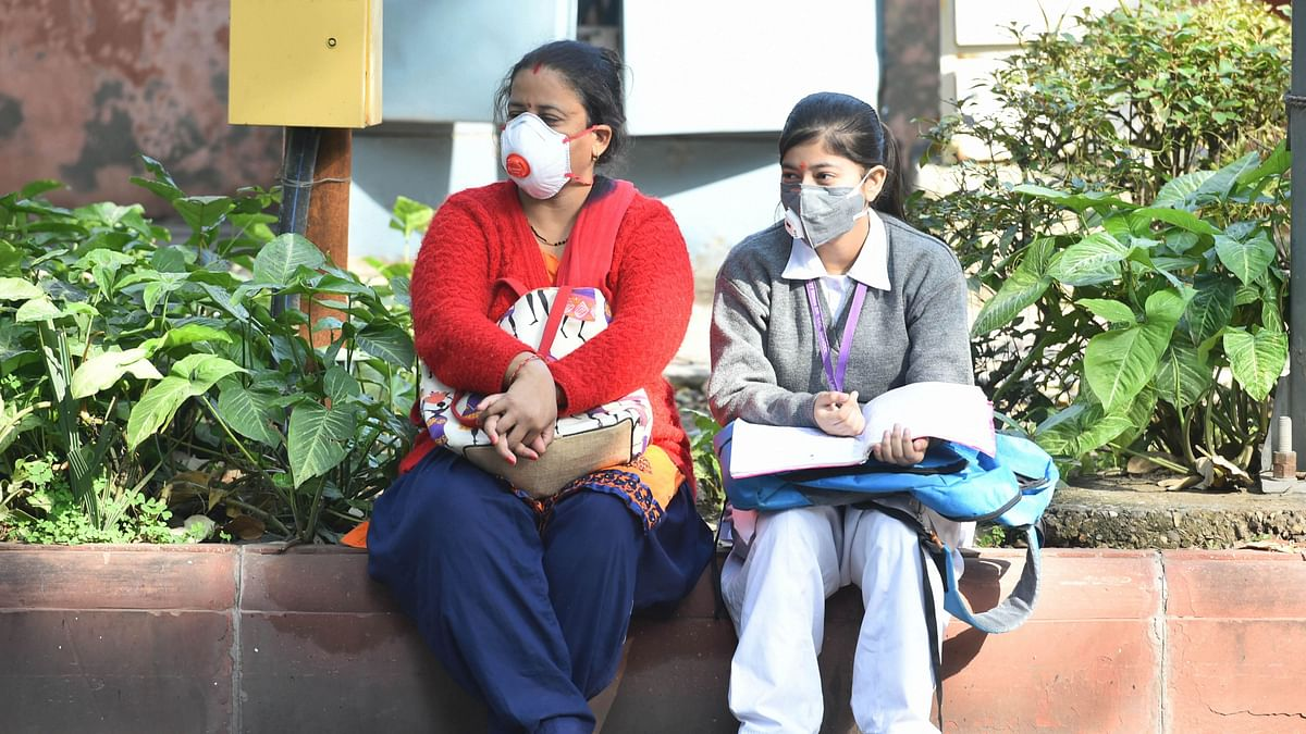 A student with her family member wear masks amid coronavirus fears, as they wait outside Kerala School ahead for their CBSE Class 10 exams, in New Delhi, Wednesday, March 18, 2020