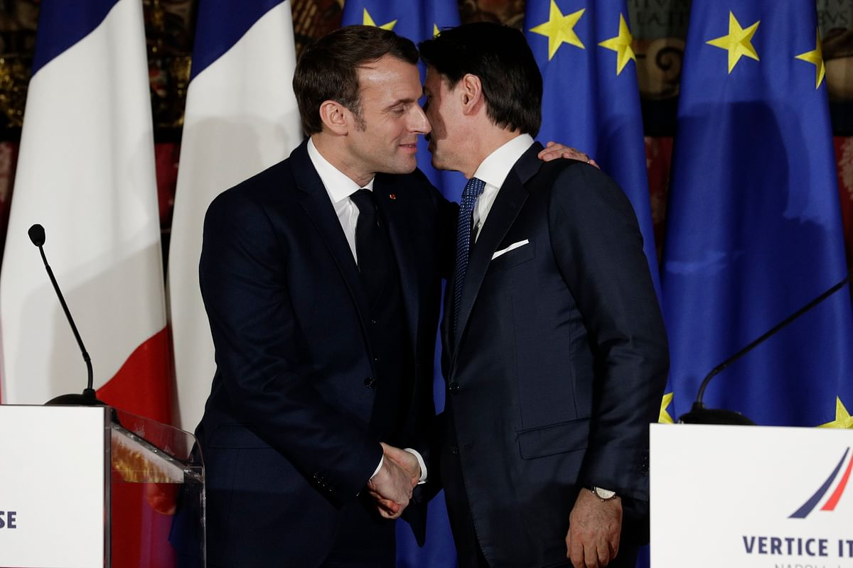 In this Thursday, Feb. 27, 2020 file photo, French President Emmanuel Macron, left, puts his arm around the shoulder of Italian Premier Giuseppe Conte and gives him a kiss on both cheeks during a joint press conference on the occasion of a French-Italian summit in Naples, southern Italy.