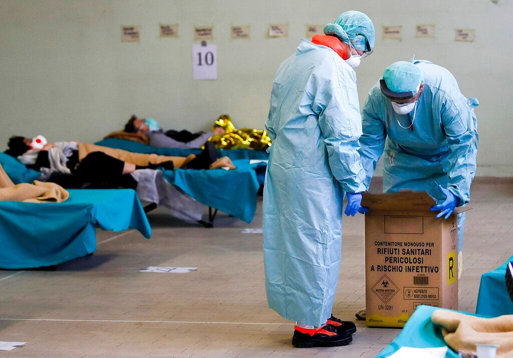 Paramedics carry an hazardous medical waste box as patients lie on camping beds, in one of the emergency structures that were set up to ease procedures in northern Italy, March 12, 2020.
