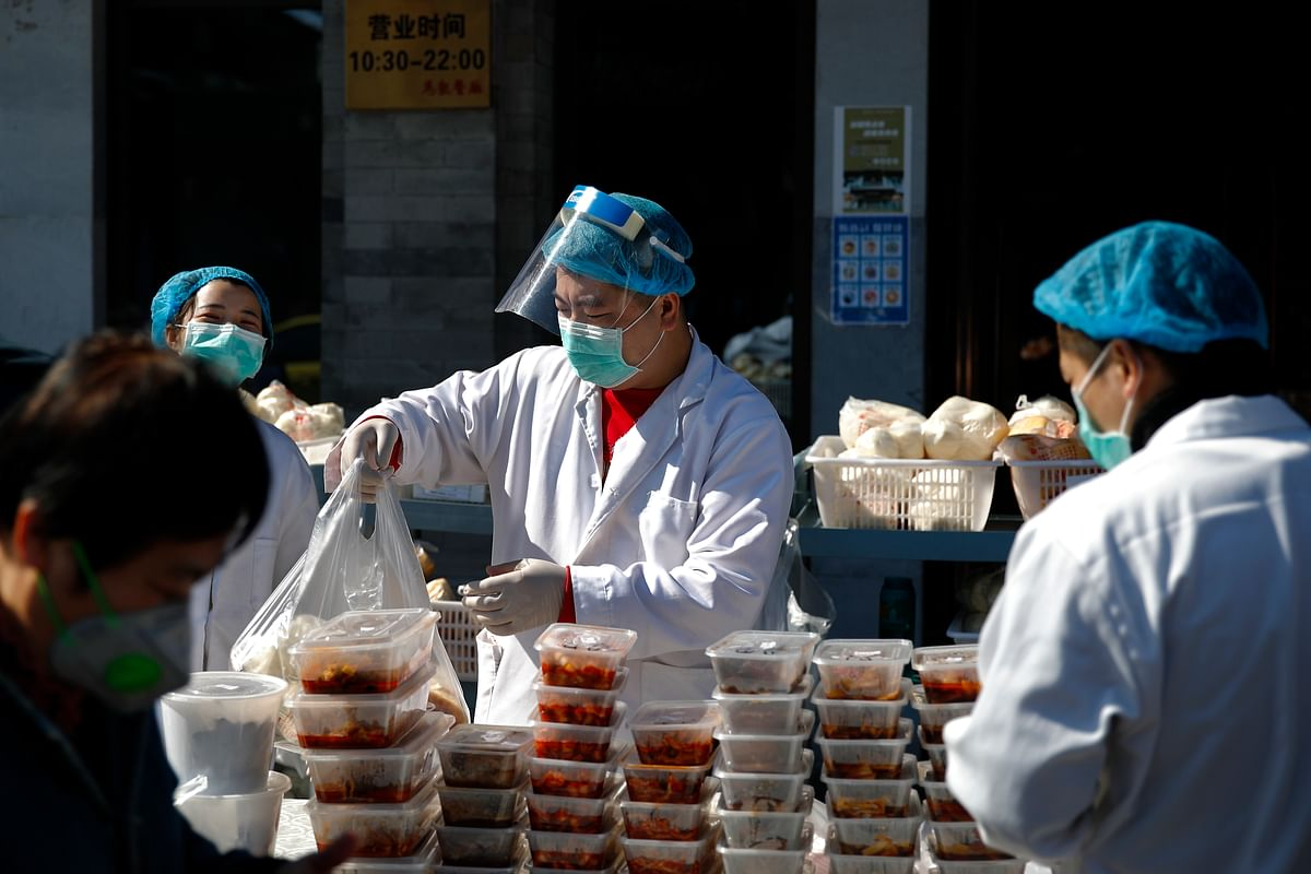 Workers wearing protective face masks pack food orders for customers outside a restaurant only offering take-out business to prevent people gathering following the coronavirus outbreak in Beijing, Sunday, March 1, 2020.