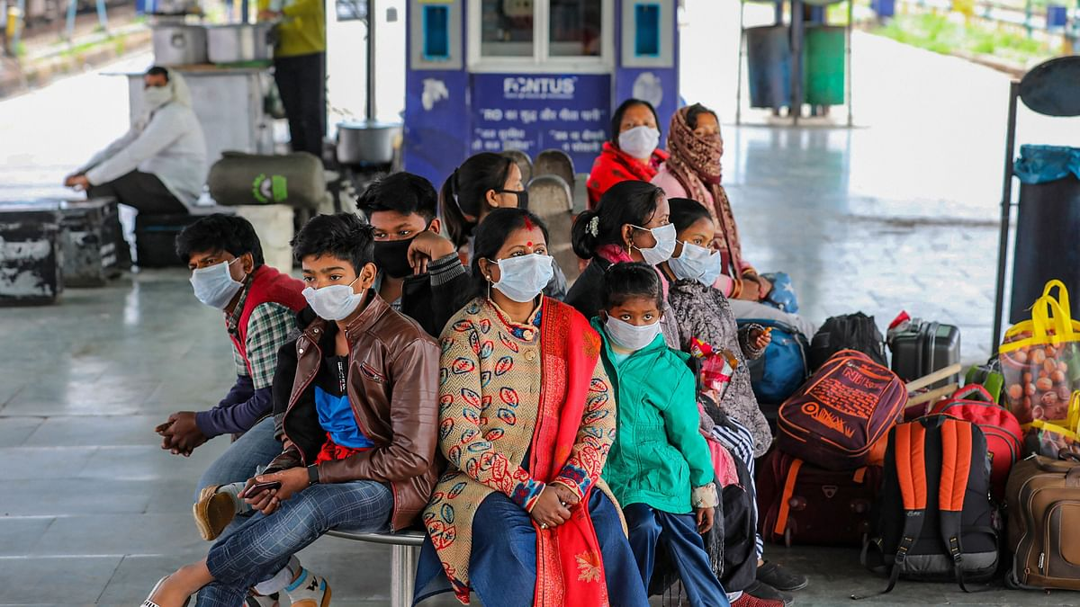 Passengers wearing protective face masks wait at a railway station following cancellation of trains in the wake of coronavirus pandemic in Jammu, Saturday, March 21, 2020.
