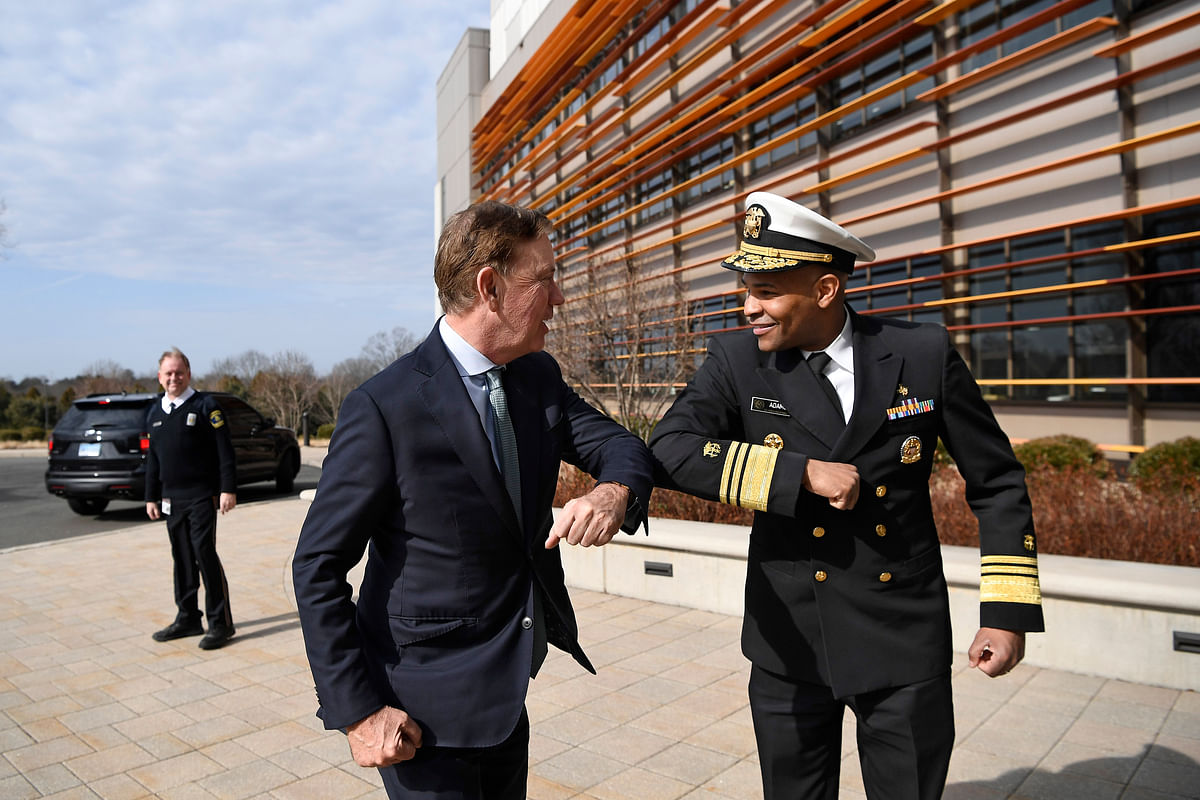 U.S. Surgeon General Vice Admiral Jerome M. Adams, right, bumps elbows with Connecticut Gov. Ned Lamont as they meet for a visit at the Connecticut State Public Health Laboratory, Monday, March 2, 2020, in Rocky Hill, Conn.