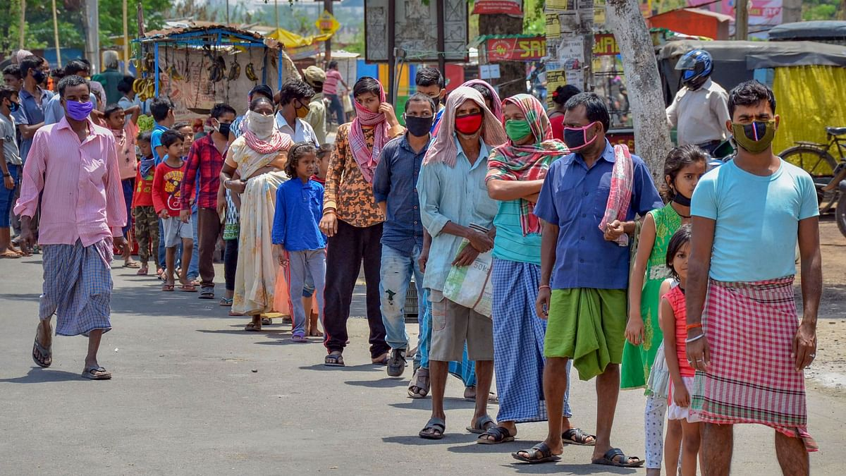 People stand in a queue to collect food from volunteers during the nationwide COVID-19 lockdown, in Ranchi on Wednesday, 15 April.