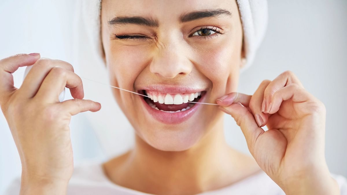 """<div class=""""paragraphs""""><p>Woman flossing her teeth.</p></div>"""